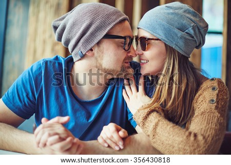 Amorous couple in caps and eyewear sitting face to face - stock photo