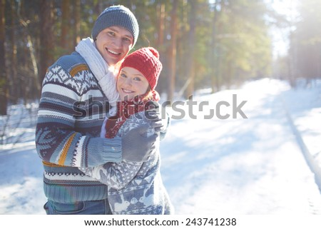 Amorous couple in casual winterwear looking at camera outdoors - stock photo