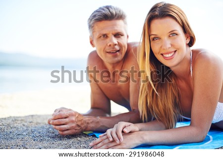 Amorous couple looking at camera while relaxing on the seaside  - stock photo