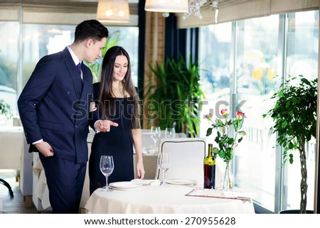 Amorous evening in the restaurant. Young couple visits a restaurant. woman holding a man's arm while the man settles a woman at the table - stock photo