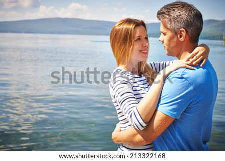Amorous man and woman standing in embrace by lake - stock photo