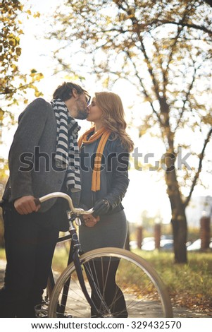 Amorous young couple with bicycle kissing in park - stock photo