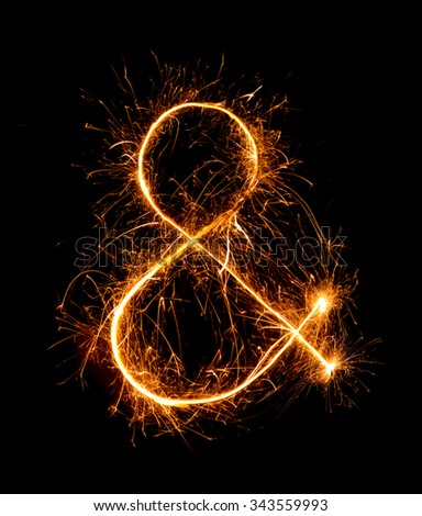 ampersand symbol  made of firework sparklers at night background