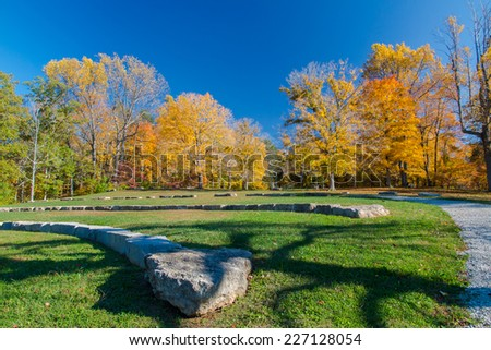 Amphitheatre in autumn park on sunny day with funny shadow from a tree. Bernheim Arboretum and Research Forest near Louisville, Kentucky, USA - stock photo