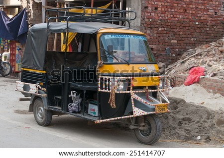 AMRITSAR, INDIA, DEC - 7, 2014:  Auto rickshaw or tuk-tuk on the street. Auto rickshaws are a common means of public transportation in India