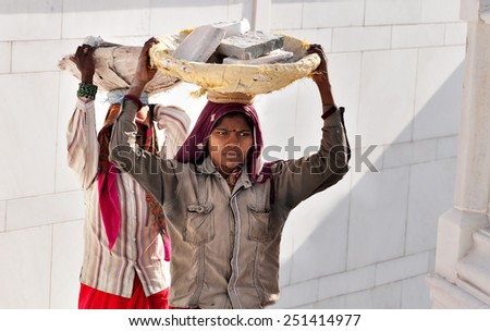 AMRITSAR, INDIA, DEC - 7, 2014: Unidentified women carry basket of stones on their head at Golden Temple (Harmandir Sahib). Golden Temple is the holiest Sikh gurdwara located in the city of Amritsar