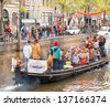 AMSTERDAM - APR 30: City natives and tourists celebrate Royal Inauguration and Queen's Day, Dutch annual national holiday, in the streets of the city, April 30, 2013, Amsterdam, The Netherlands - stock photo