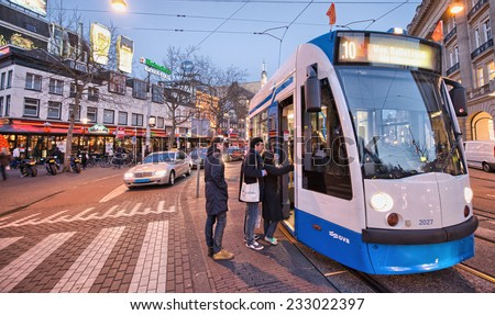 AMSTERDAM - APR 30: Tram running in the city centre amongst pedestrians, April 30, 2013 in Amsterdam. The tram network comprises 16 lines and covers 213 kilometres
