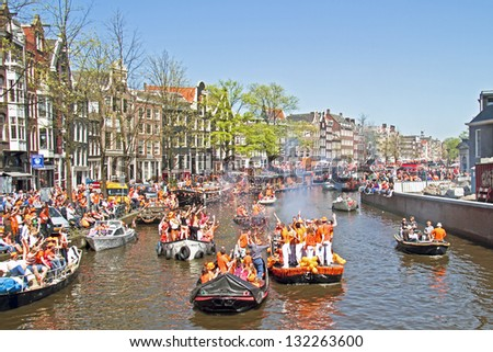 AMSTERDAM - APRIL 30: Amsterdam canals full of boats and people in orange during the celebration of queensday on April 30, 2012 in Amsterdam, The Netherlands - stock photo