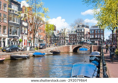 AMSTERDAM-APRIL 30: Amsterdam cityscape with row of cars, bikes and boats parked along the Amsterdam canal during the sunny day on April 30,2015, the Netherlands. - stock photo
