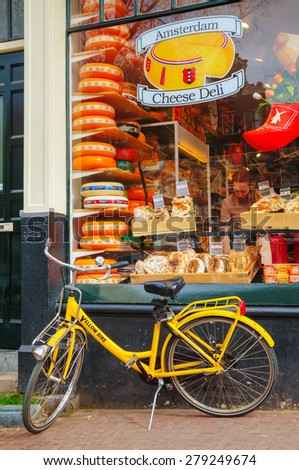 AMSTERDAM - APRIL 16: Bicycle parked near a grocery store on April 16, 2015 in Amsterdam, Netherlands. It's the capital city and most populous city of the Kingdom of the Netherlands. - stock photo