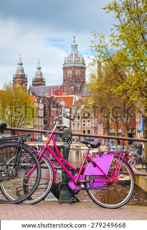 AMSTERDAM - APRIL 16: Bicycles parked at the bridge on April 16, 2015 in Amsterdam, Netherlands. It's the capital city and most populous city of the Kingdom of the Netherlands. - stock photo