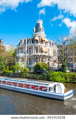 Amsterdam-April 30: Boat Cruising on Amsterdam Singelgrachtkering Canal on April 30,2015, tourists enjoy sightseeing, the Netherlands.