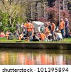 AMSTERDAM - APRIL 30: City natives and tourists celebrate Queen's Day, Dutch annual national holiday, in the streets of the city, April 30, 2012, Amsterdam, The Netherlands - stock photo
