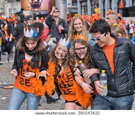 AMSTERDAM - APRIL 30: City natives and tourists celebrate Queen's Day, Dutch annual national holiday, in the streets of the city, on April 30, 2013 in Amsterdam, The Netherlands.