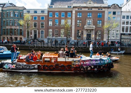 AMSTERDAM - APRIL 27: Open air party through Amsterdam canals during King's Day on April 27,2015. the Netherlands. Kings Day is the biggest festival celebrating the birth of Dutch royalty.