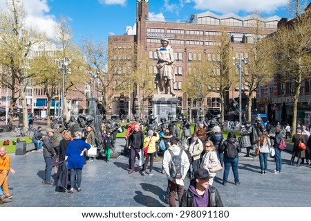 Amsterdam-April 30: Rembrandtplein with a bronze-cast representation The Night Watch, by Mikhail Dronov and Alexander Taratynov, tourists see the sights on April 30, 2015, the Netherlands. - stock photo