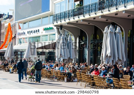 Amsterdam-April 30: Undefined people have drinks in outdoor cafe with Rembrandtplein view, famous Escape club is visible in the background on April 30,2015, the Netherlands. - stock photo