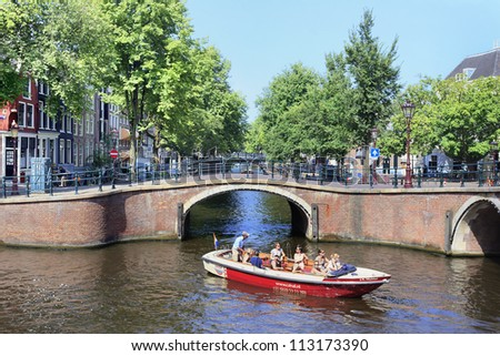 AMSTERDAM-AUG. 19, 2012. Boat with tourists Aug. 19, 2012 in Amsterdam. The city is known as Venice of the North, its beautiful canal belt was finally added to the world heritage list in July 2010. - stock photo
