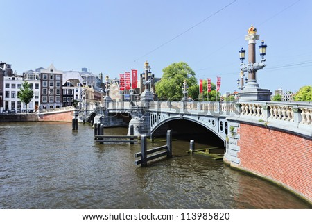AMSTERDAM-AUG. 19, 2012. Ornate ancient bridge on Aug. 19, 2012 in Amsterdam. It is known as Venice of the North, its beautiful canal belt was finally added to world heritage list in July 2010. - stock photo