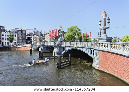 AMSTERDAM-AUG. 19: Ornate ancient bridge on Aug. 19, 2012 in Amsterdam. It is known as Venice of the North, its beautiful canal belt was finally added to world heritage list in July 2010. - stock photo