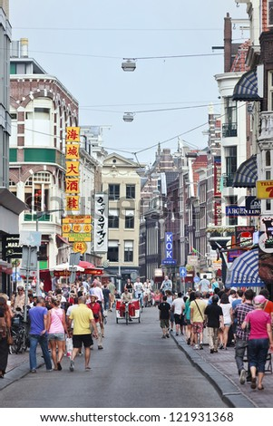 AMSTERDAM-AUG. 19: Tourists in The Damstraat. The city has 15,749,000 annual visitors,  37,763 hotel beds, 6,800 16th-, 17th- and 18th-century buildings and 51 museums. Amsterdam, Aug. 19, 2012. - stock photo
