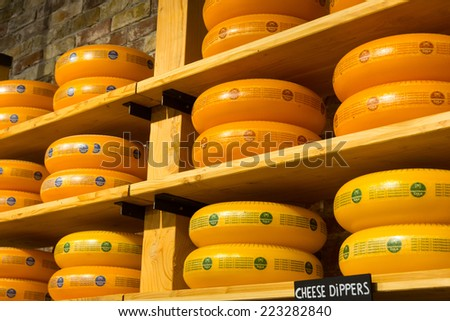 AMSTERDAM - AUGUST 25: Cheese wheels are on the shelves in the store on August 25, 2014 in Amsterdam. - stock photo