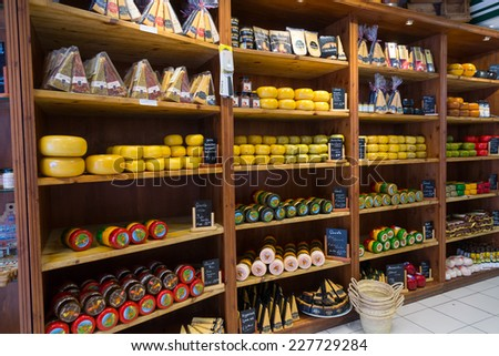 AMSTERDAM - AUGUST 26: Cheese wheels are on the shelves in the store on August 26, 2014 in Amsterdam. - stock photo