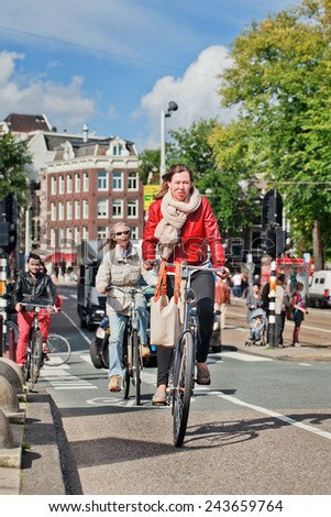 AMSTERDAM-AUGUST 27, 2014. Dutch people on their bicycle. In a city with 800,000 people, there are 880,000 bicycles, the municipal government estimates, which is four times the number of its cars - stock photo