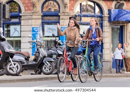 AMSTERDAM-AUGUST 26, 2014. Dutch pretty girls on a bicycle. In a city with 800,000 people, there are 880,000 bicycles, the municipal government estimates, which is four times the number of its cars.