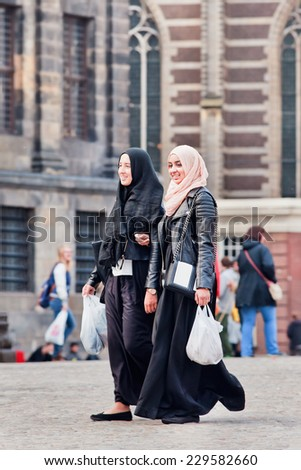 AMSTERDAM-AUGUST 26, 2014. Exotic Muslim girls on the Dam Square. There are an estimated 1.2 million Muslims in the Netherlands, which is equivalent to about 6 percent of the country's population. - stock photo