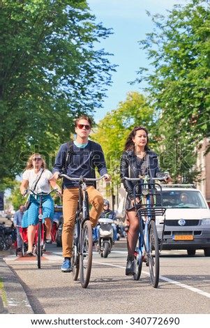 AMSTERDAM-AUGUST 27, 2014. Fashionable citizens on bicycles. In a city with 800,000 people, there are 880,000 bicycles, the municipal government estimates, which is four times the number of its cars.