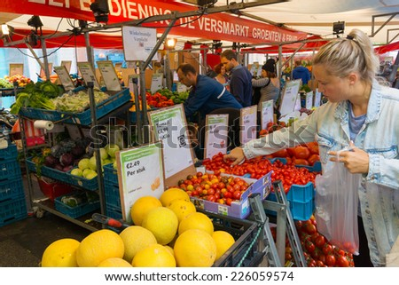 AMSTERDAM - AUGUST 30: People buy vegetables at the market on August 30, 2014 in Amsterdam.