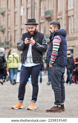 AMSTERDAM-AUGUST 26, 2014. Trendy Asian tourists on Dam Square. Amsterdam is the most visited Dutch city (4.3 million foreign guests). Several times a week events are being organized on Dam Square. - stock photo