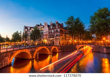 Amsterdam Canal and Light Trails of a Vessel - stock photo