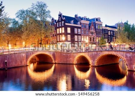Amsterdam canal bridges illuminated at evening, Netherlands, North Holland province. - stock photo