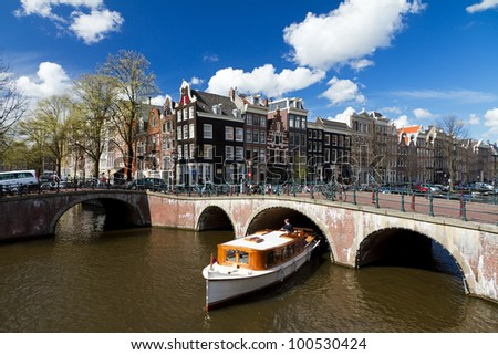 Amsterdam canal intersection with white boat - stock photo