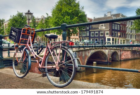 Amsterdam canal scene with a pink bicycle and brick bridges. - stock photo
