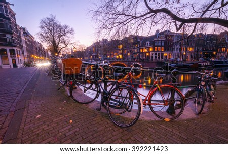 Amsterdam canal view, bicycles on the bridge. Evening time. Sunset light