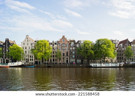 Amsterdam canal with boats and houses - stock photo