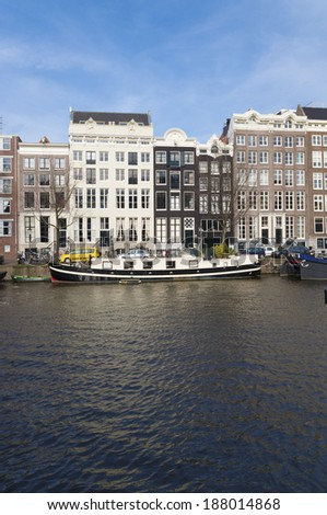 amsterdam canal with historical houses. Most of them are very small, because in earlier ages the tax was levied on the basis of the width of the facade. - stock photo