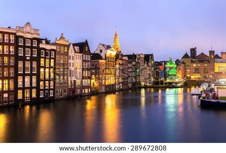Amsterdam Canals and Saint Nicholas church at dusk Natherland - stock photo