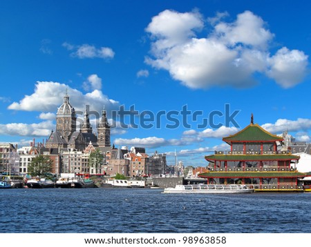 Amsterdam, capital city of Netherlands. Historical church and famous floating Chinese restaurant in beautiful weather. - stock photo
