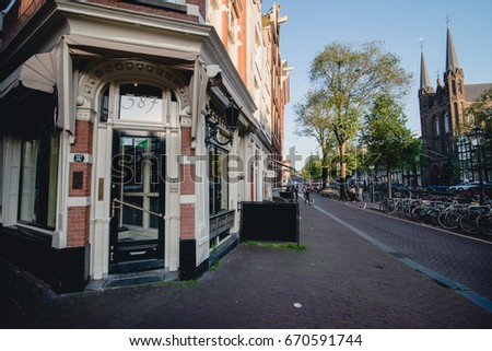 AMSTERDAM - CIRCA JUNE 2017: view of a street along the canal with traditional dutch building facades in the center of Amsterdam, The Netherlands in June 2017.