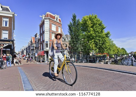AMSTERDAM. 18: Cyclist on Aug. 18, 2012 in Amsterdam. Bicycles outnumber the people in Amsterdam: 760,000 citizens and nearly a million bikes. There are also twice as many bikes then cars. - stock photo