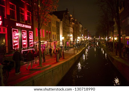 AMSTERDAM - DEC 3: Red Light District on December 3, 2012 in Amsterdam. It is the city's most famous tourist spot. There are over 500 windows in the city and about 1000 working girls. - stock photo