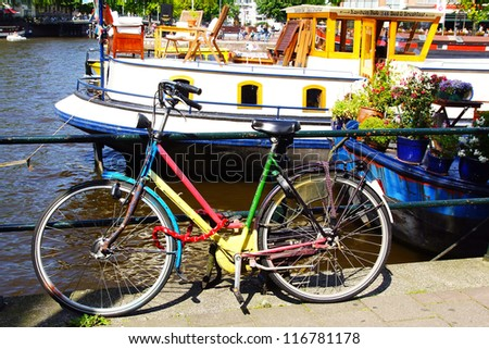 AMSTERDAM, HOLLAND - AUGUST 01:Dutch scenery with bike and housboat. A houseboat is a boat that has been designed or modified to be used as a human dwelling; August 01, 2012 Amsterdam, Holland