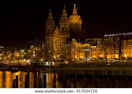 Amsterdam, Holland - December 28, 2015: Illuminated Saint Nicholas church at night and people waiting at tram stop in Amsterdam, Holland on December 28, 2015 - stock photo