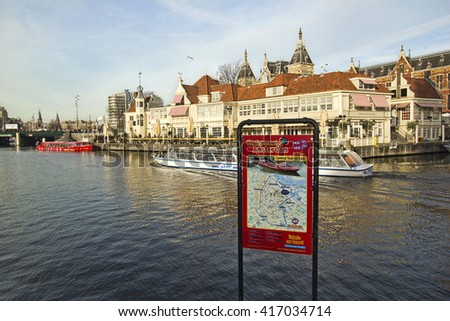 Amsterdam, Holland - December 28, 2015: Tour boat with tourists sail by the central railway station in Amsterdam, Holland on December 28, 2015 - stock photo