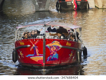 Amsterdam, Holland - November 12, 2015: Canal boat with tourists and paintings of Van Gogh sails in a canal in the red light district of Amsterdam on November 12, 2015 in Amsterdam, Holland.